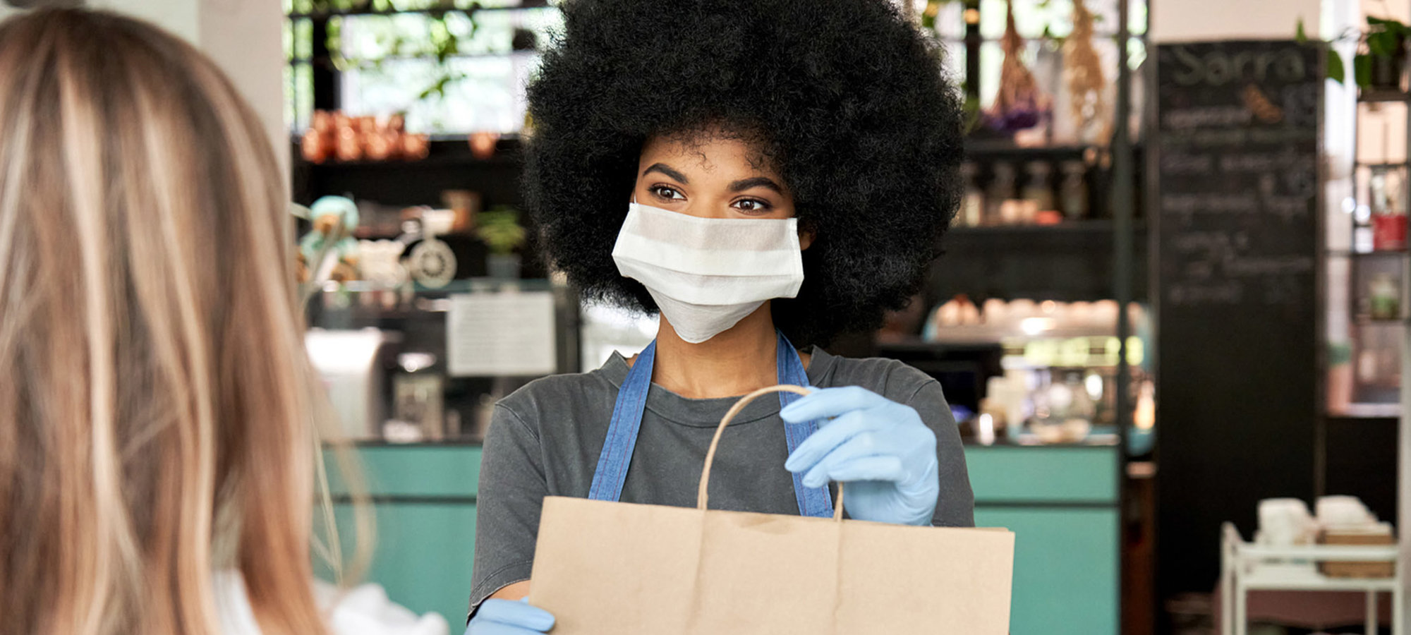 Employee wearing mask handing bag to customer
