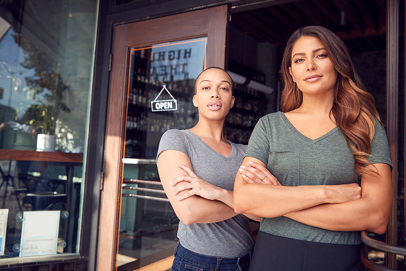 Two women standing in front of coffee shop